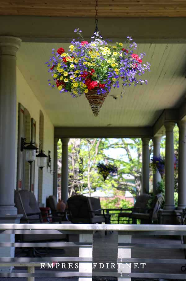 Cone-shaped hanging wicker basket with brightly-colored flowers on front porch.