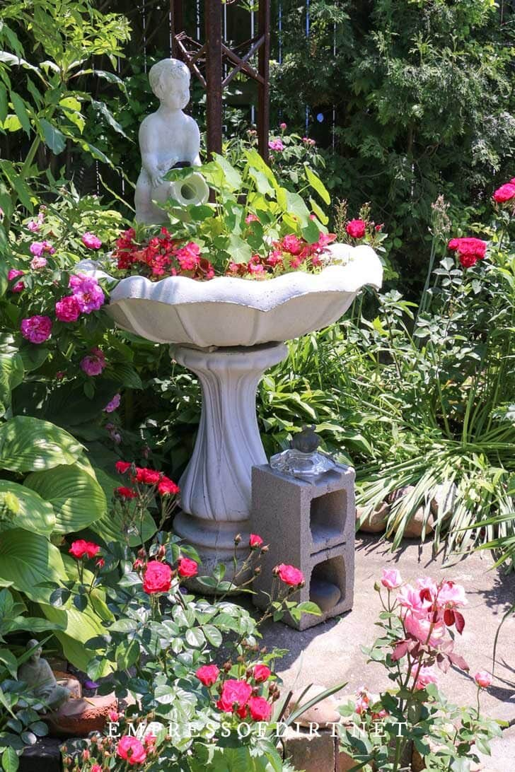 Birdbath planted with pink flowers and green foliage with angel statue in background.