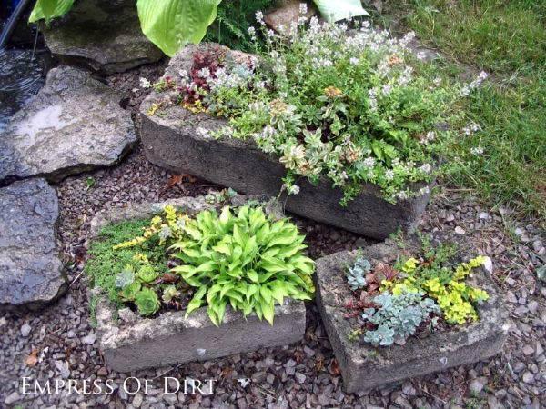 Concrete hypertufa planters in garden.