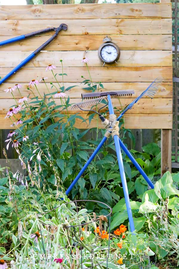 Blue handled garden tools tied together as garden trellis.