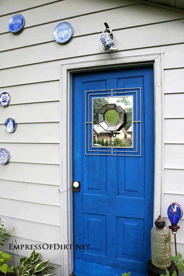 Mirror and candle holder on blue shed door.