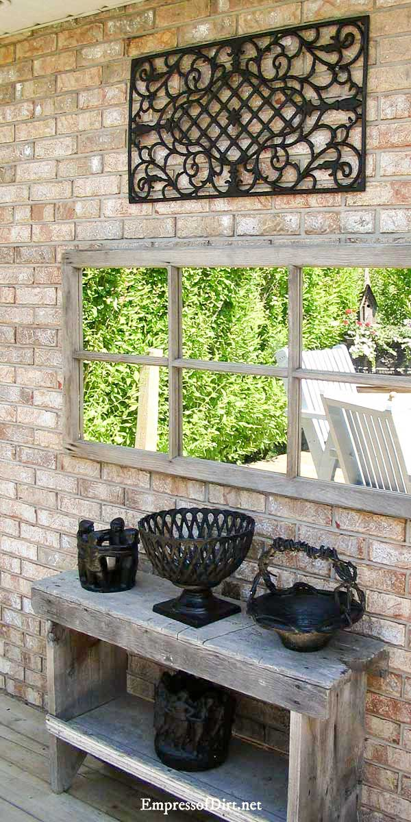 Unfinished wood frame mirror on patio with bench.