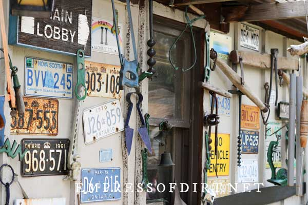 Licence plates on wall of shed with old tools.