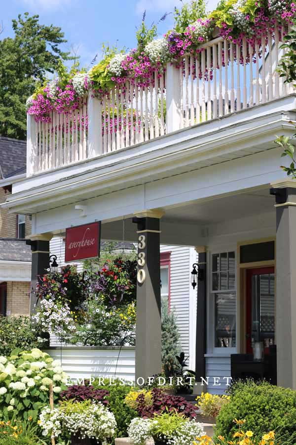 Upper and lower front porches with flowering annuals in baskets.