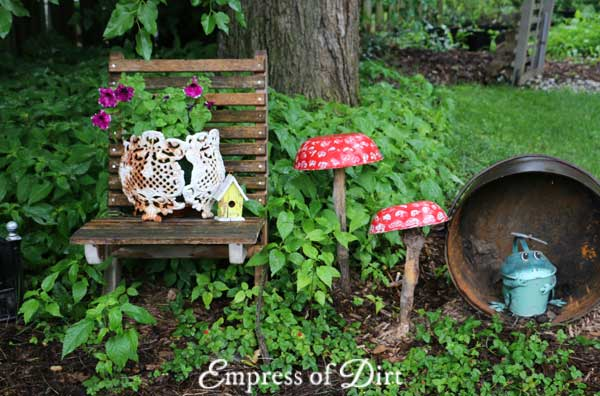Garden art and chair in backyard garden.