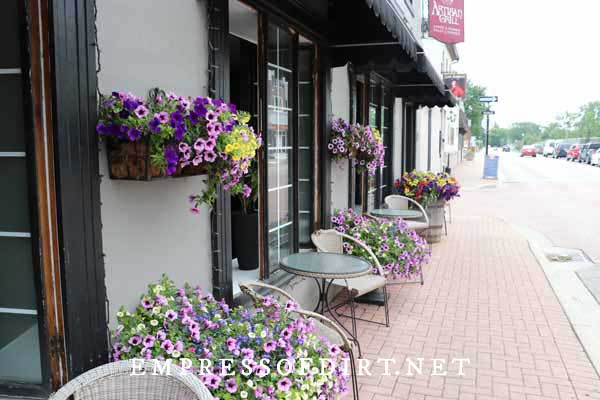 Sidewalk cafe with beautiful containers of flowering annuals.
