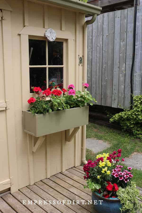Window box with pink and red geraniums on front of shed.