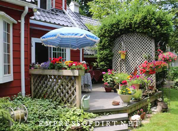 Backyard patio with a collection of flower pots filled with colorful annuals.