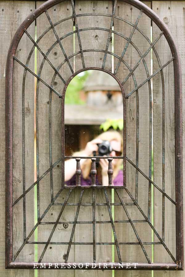 Garden art mirror on fence.