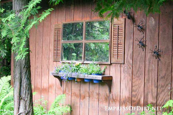 Faux window on shed wall made from frame mirrors and shutters.