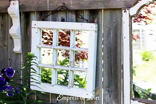 White framed mirror on garden fence.