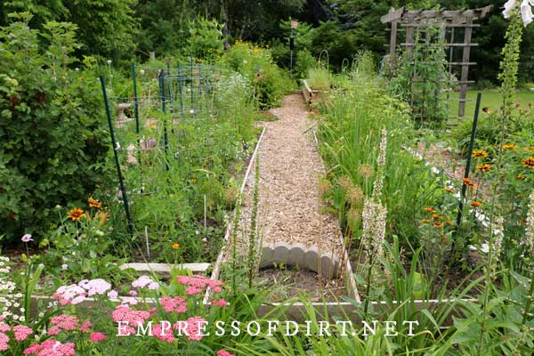 Vegetable and flower beds surrounded by pea gravel walkways.