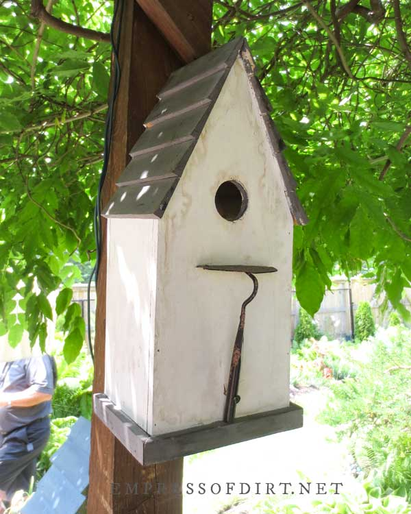 White birdhouse with trowel perch.