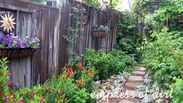 Garden with lilies, flowering annuals, and stone pathway and edging.