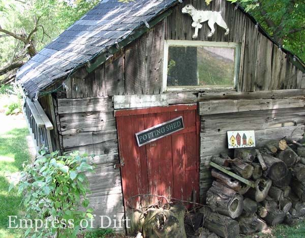 Rustic old garden shed with garden art dog and sign saying 'potting shed'.