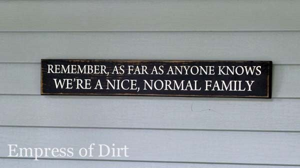 Garden sign saying 'remember, as far as anyone knows we're a nice, normal family.'