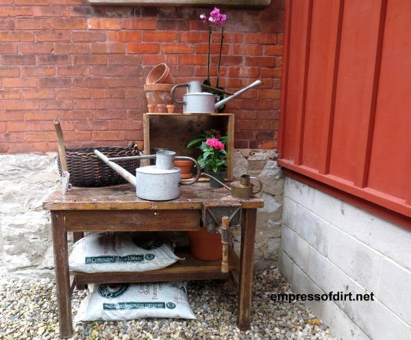 A sturdy old table does double duty as a potting bench.