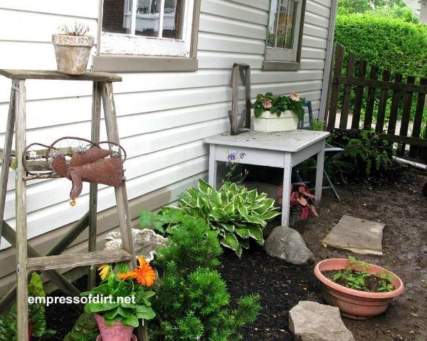 Painted table in garden used as potting bench.