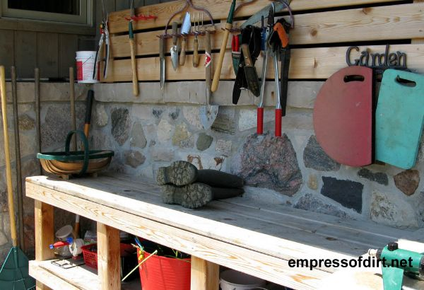 Wooden potting bench with storage shelf underneath.
