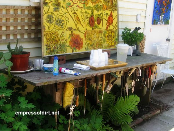 Potting bench in garden with colorful tile.