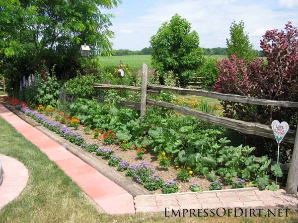 Country vegetable and flower garden surrounded by brick pavers.
