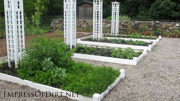 White raised garden beds with tall white trellis.