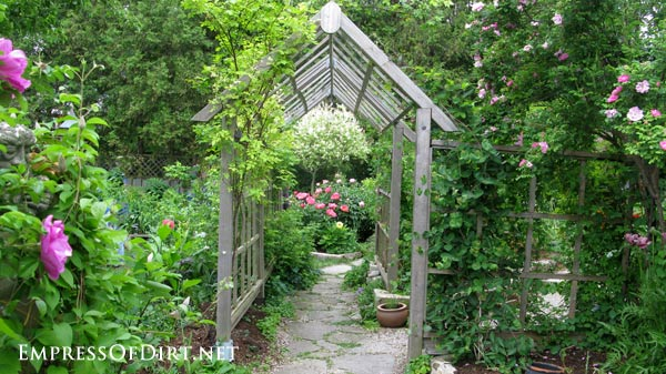 20+ Ways to create vertical interest in the garden with arbors, trellis, obelisks, and more. This arbor walkway is in the rose garden.