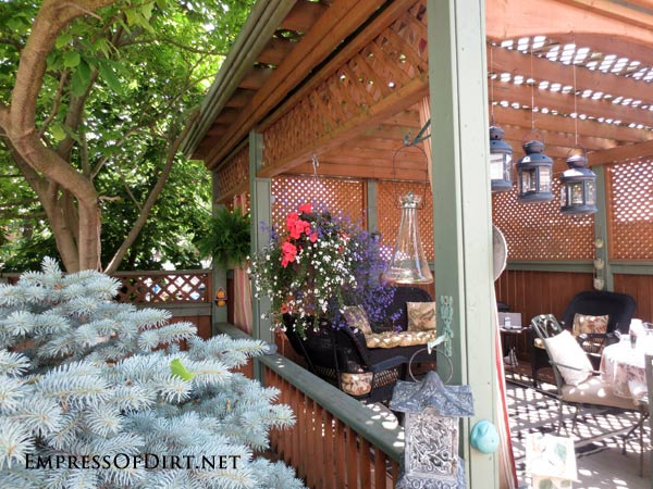 20+ Ways to create vertical interest in the garden with arbors, trellis, obelisks, and more. This shaded seating area has a trellis roof.