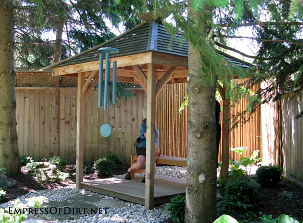20+ Ways to create vertical interest in the garden with arbors, trellis, obelisks, and more. This seating area adds a focal point amongst the tall pines.