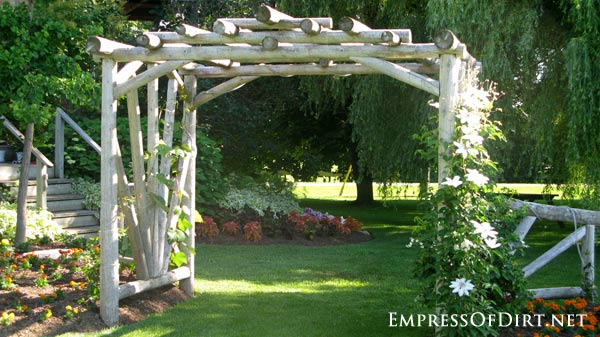 20+ Ways to create vertical interest in the garden with arbors, trellis, obelisks, and more. This arbor is made from logs.