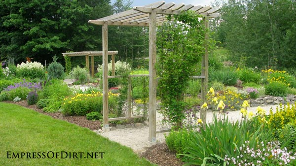 20+ Ways to create vertical interest in the garden with arbors, trellis, obelisks, and more. Arbor in the perennial garden.