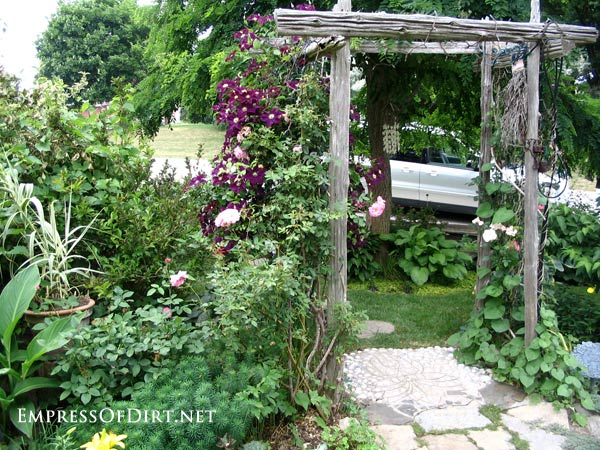 20+ Ways to create vertical interest in the garden with arbors, trellis, obelisks, and more. Rustic wood arbor.