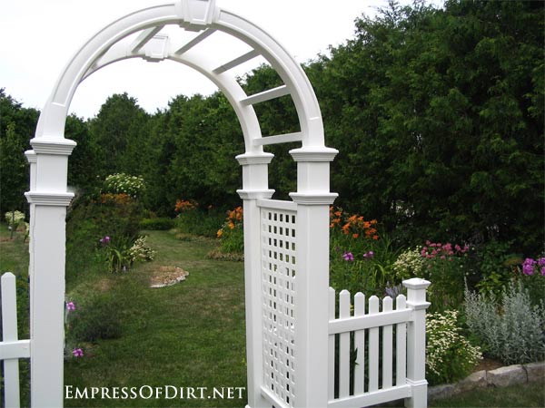 20+ Ways to create vertical interest in the garden with arbors, trellis, obelisks, and more. Classic white arched arbor.