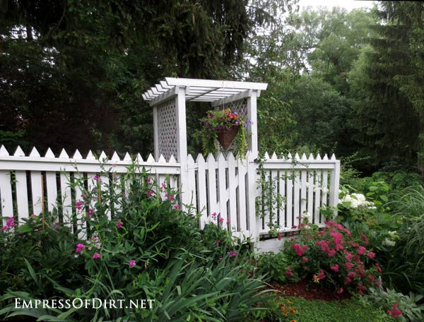 20+ Ways to create vertical interest in the garden with arbors, trellis, obelisks, and more. White arbor with picket fence.