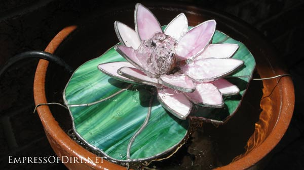 Backyard pond and water feature ideas: stained glass lily in a watertight pot.