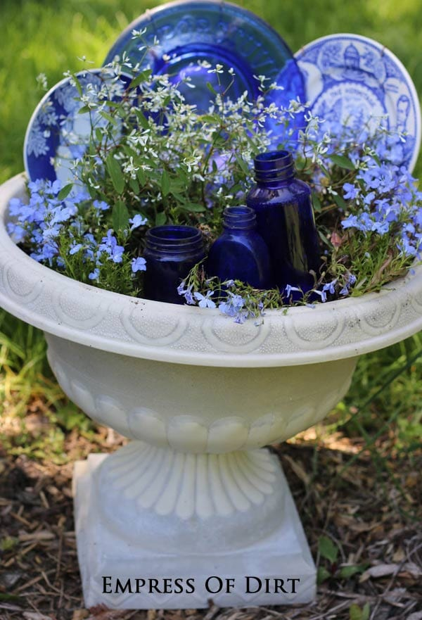 Blue and white plates and bottles in a garden planter | empressofdirt.net