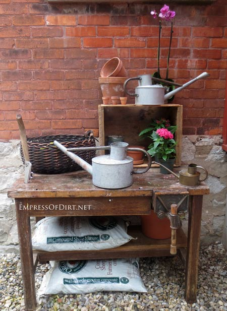 Potting table with watering can collection