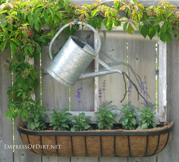 Watering can over window box on fence