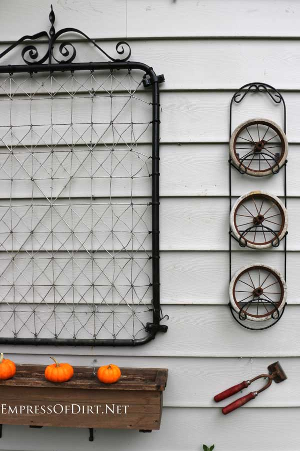 Old garden gate and doll carriage wheels on garden shed wall| empressofdirt.net