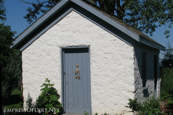 Rutic, white plaster shed from Creative garden shed ideas at empressofdirt.net