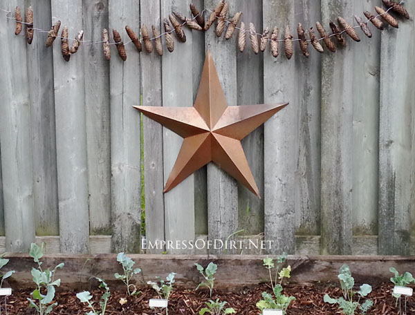 Pinecone garland in the garden | 15 Pinecone Craft and Decor Projects including fairies, tiny animals, fire starters, wreaths, ornaments, and more.
