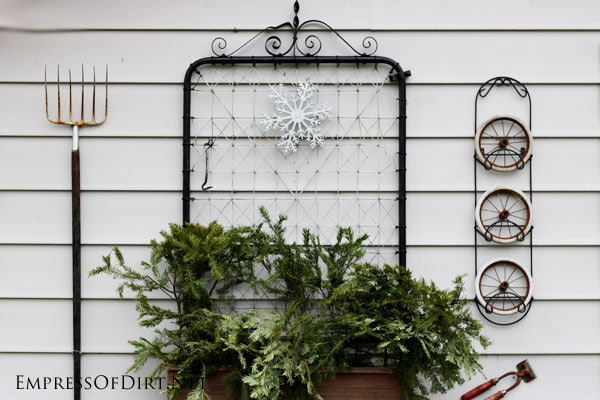 Rustic garden shed decorated for winter with greenery, snowflake, berry wreath, and lights