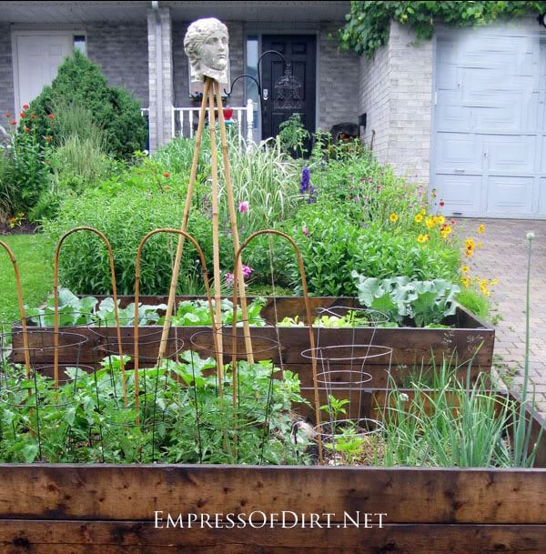 Raised garden beds on a small city lot providing room for lots of flowers and veggies on a sloped yard.