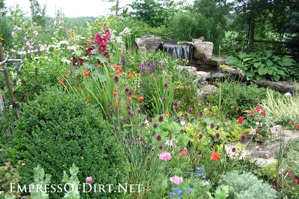 Country garden in Ontario, Canada with a cottage-style flower beds and waterfall