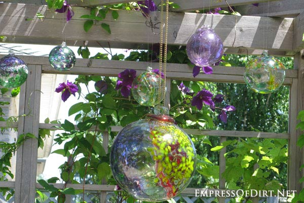 Kick your garden up a notch with these 12 Colourful Garden Ideas at empressofdirt.net. Here glass bubbles hang from the arbor adding beautiful colours.