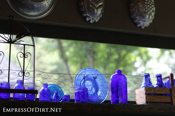 Kick your garden up a notch with these 12 Colourful Garden Ideas at empressofdirt.net. This collection of blue glass bottles brightens up the patio.