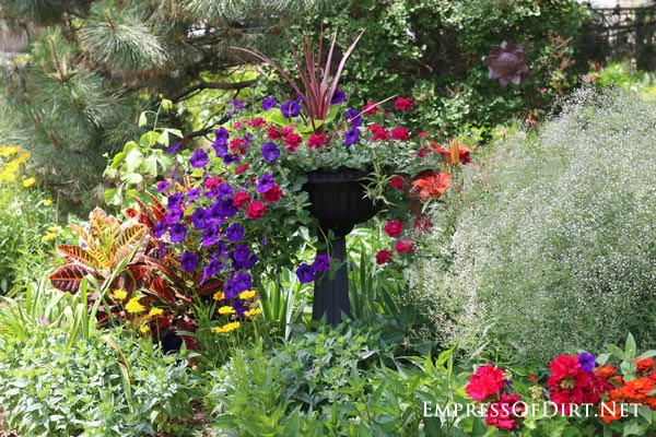 Kick your garden up a notch with these 12 Colourful Garden Ideas at empressofdirt.net. This planter is spilling over with eye-popping red and purple petunias.