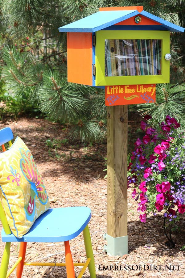 Kick your garden up a notch with these 12 Colourful Garden Ideas at empressofdirt.net. This beautiful front garden has eye-popping, contrasting colours and a neighbourhood book box.