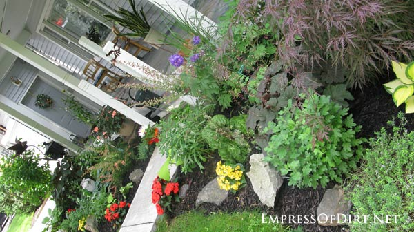Kick your garden up a notch with these 12 Colourful Garden Ideas at empressofdirt.net. This beautiful front garden has eye-popping, contrasting colours and an assortment of garden art on the porch.