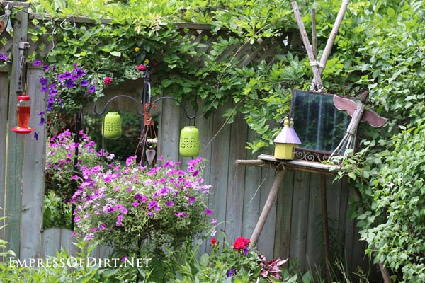 Kick your garden up a notch with these 12 Colourful Garden Ideas at empressofdirt.net. This back garden has bird feeders in an assortment of colours.